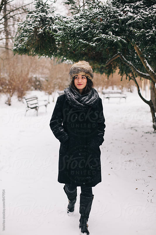 Beautiful woman walking through the park during a snowy day by VeaVea for Stocksy United