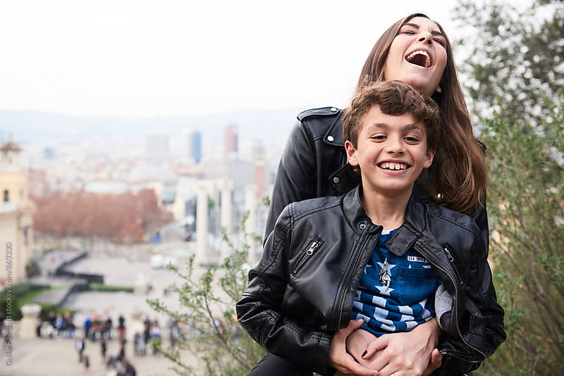 Sister and brother laughing together. Barcelona by Guille Faingold for Stocksy United