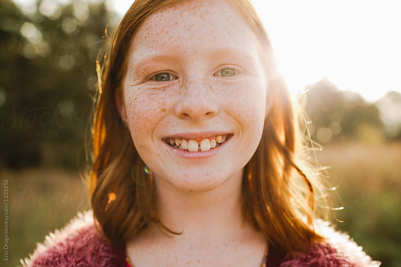 redheaded girl smiling in the sun by Erin Drago for Stocksy United