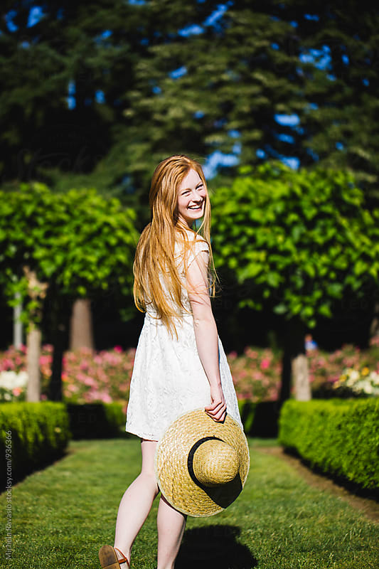 Happy young woman with long red hair enjoying the nature in a sunny day by michela ravasio for Stocksy United