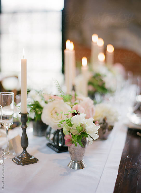 Floral arrangements and candlesticks on a formal dinner table by Marta Locklear for Stocksy United
