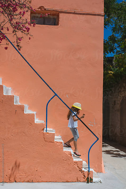 Child walking down the stairs. by Dejan Ristovski for Stocksy United