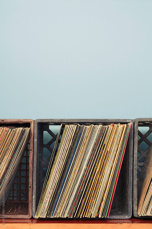 Vinyl record albums in milk crates against a blue wall by David Smart for Stocksy United