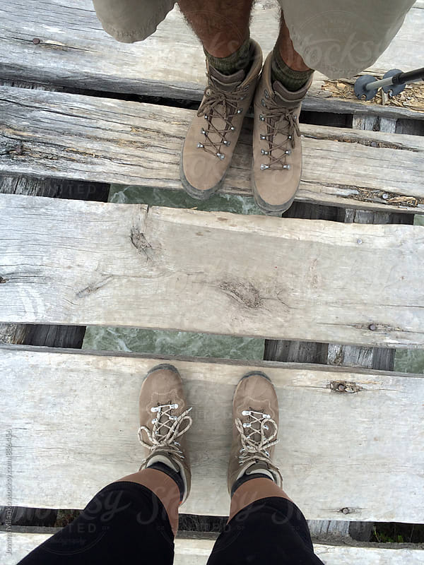 Man and woman trackers standing on a wooden bridge above the river in all terrain shoes by Jovana Milanko for Stocksy United