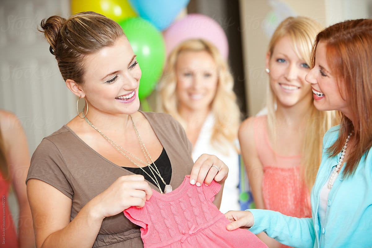 Baby Shower Pregnant Mom And Friend Laugh Over Cute Clothing By Sean Locke Party Shower Stocksy United