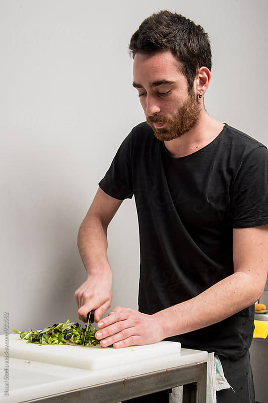 Young man cutting vegetables in the kitchen of a restaurant by Bisual Studio for Stocksy United