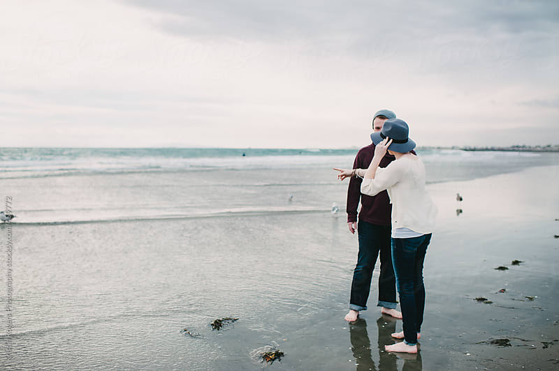 Cute couple exploring and gathering shells on cloudy  beach by Kristin Rogers Photography for Stocksy United