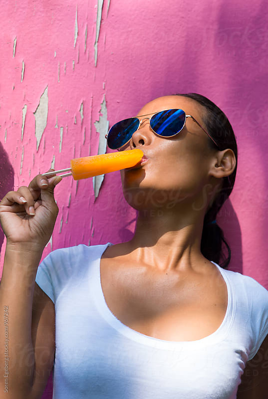 Summer portrait of young beautiful woman eating an orange popcicle on pink background by Soren Egeberg for Stocksy United