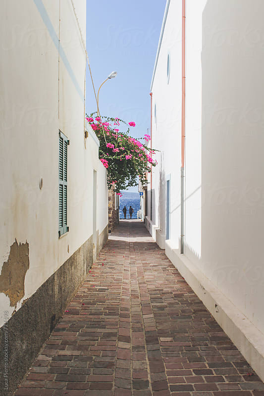 A couple walking in a beautiful alley in Portugal by Luca Pierro for Stocksy United