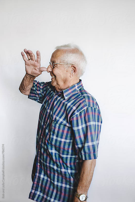 Goofy senior manmaking faces on white background by Rob and Julia Campbell for Stocksy United