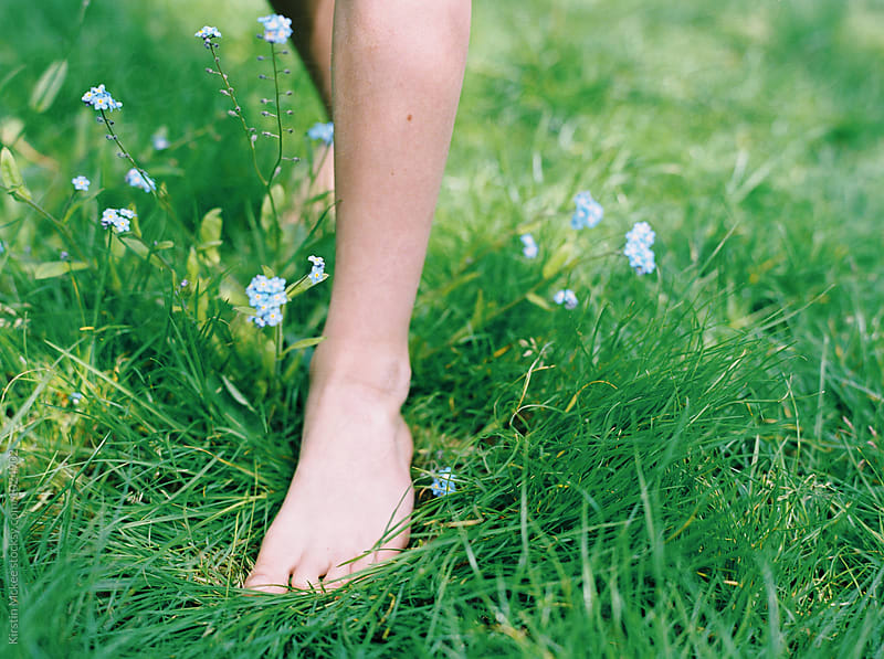 Boy's feet walking through forget me nots by Kirstin Mckee for Stocksy United