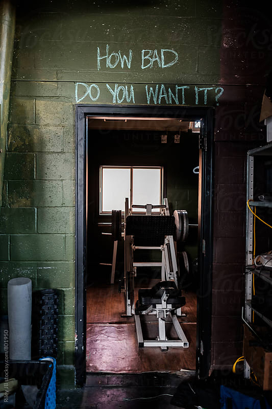 'How bad do you want it?' written in chalk over a door in a gritty gym. by Riley Joseph for Stocksy United