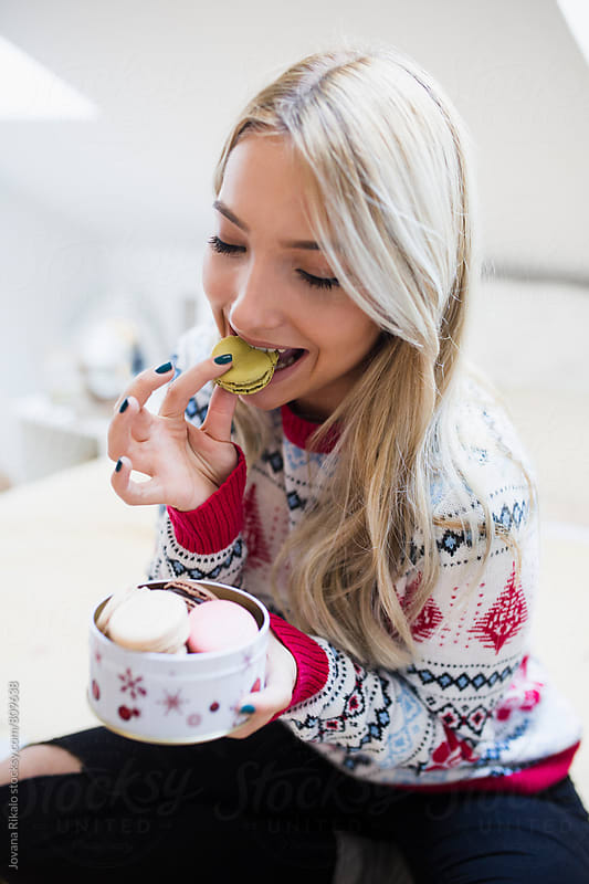 Young woman eating french macaroons by Jovana Rikalo for Stocksy United