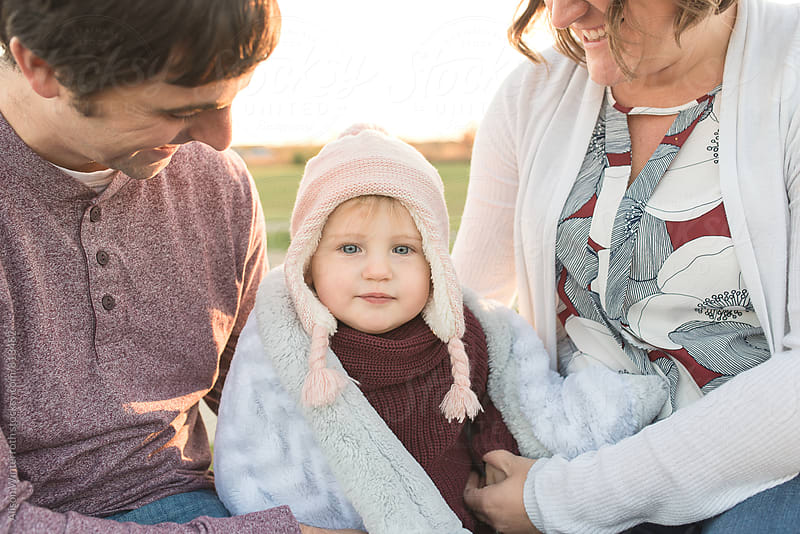 A Mother And Father Smile At Their Bundled Up Daugther by Alison Winterroth for Stocksy United