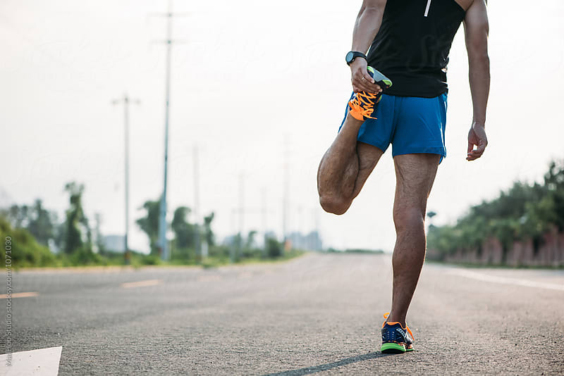 Runner stretching leg on road by Maa Hoo for Stocksy United