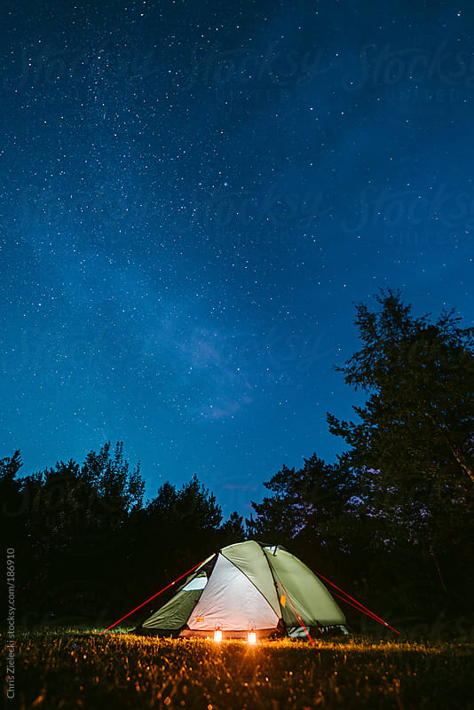 Tent with candles under the stars by Christian Zielecki for Stocksy United