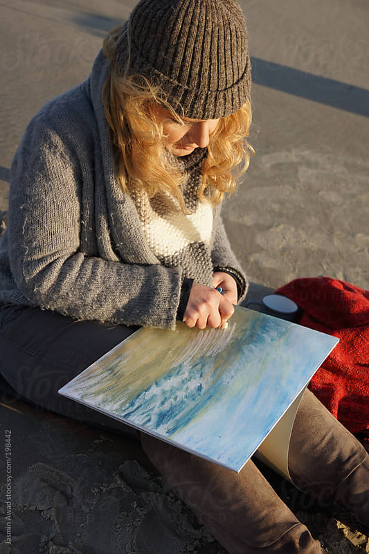 Artist painting at the beach by Jasmin Awad for Stocksy United
