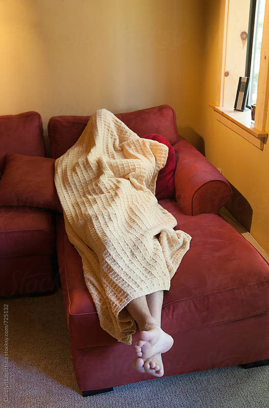 Man sleeping on the couch covered in a yellow blanket by Carolyn Lagattuta for Stocksy United