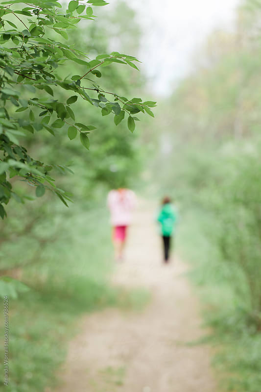 Two girls (in the distance) walking along a path in the spring by Amanda Worrall for Stocksy United