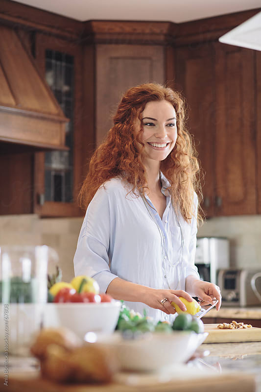 Happy young woman in the kitchen preparring vegetables in the ki by Ania Boniecka for Stocksy United