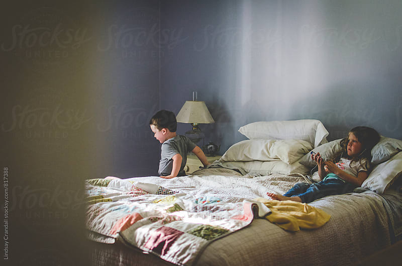 Two children on a bed by Lindsay Crandall for Stocksy United