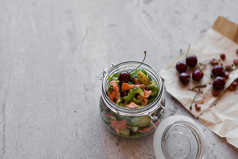 Jar with brussel sprout, salmon and cherry salad by Nadine Greeff for Stocksy United