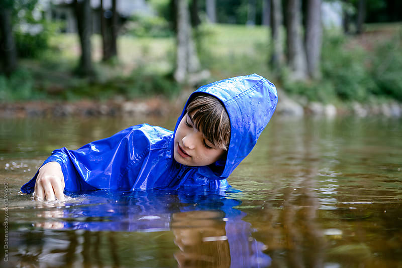 Child wears a raincoat while swimming in a lake by Cara Dolan for Stocksy United