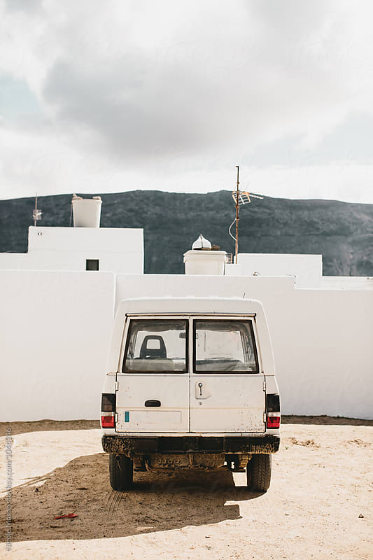white vehicle on sand with white buildings in desert landscape by Nicole Mason for Stocksy United
