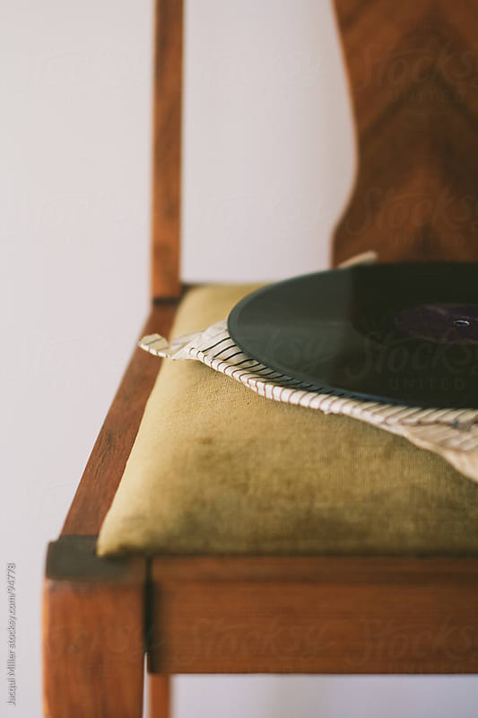 An old record on an antique chair by Jacqui Miller for Stocksy United