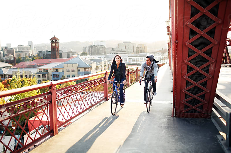 Two people riding bikes across bridge in the evening by Isaac Lane Koval for Stocksy United