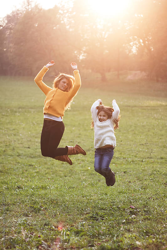 Two girls jumping and having fun in park by Jovana Rikalo for Stocksy United
