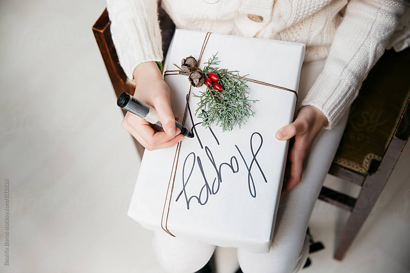 Woman writing Happy holidays on a Christmas present box by Beatrix Boros for Stocksy United