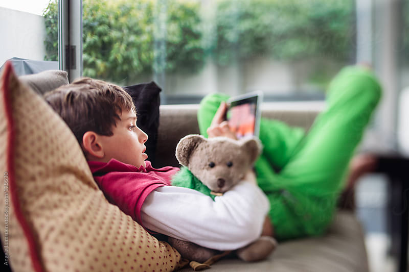 Boy using a tablet while holding a teddy bear by Angela Lumsden for Stocksy United