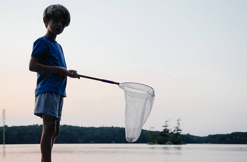 Boy with net plays near a lake at sunset by Cara Dolan for Stocksy United