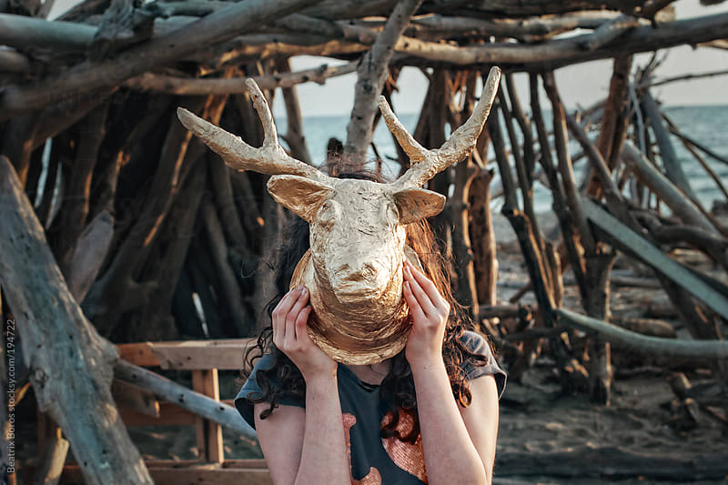 Girl holding a homemade deer head in front of her face on the beach by Beatrix Boros for Stocksy United