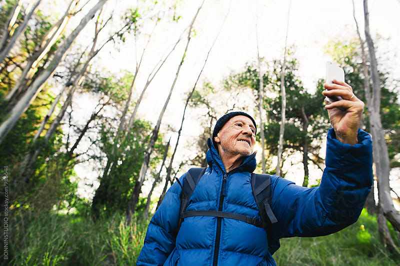 Hiker senior man taking a photo in the woods.  by BONNINSTUDIO for Stocksy United
