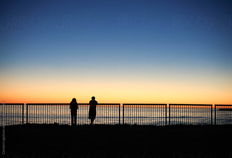 Male and female silhouettes watching the sun set over the ocean by Carolyn Lagattuta for Stocksy United