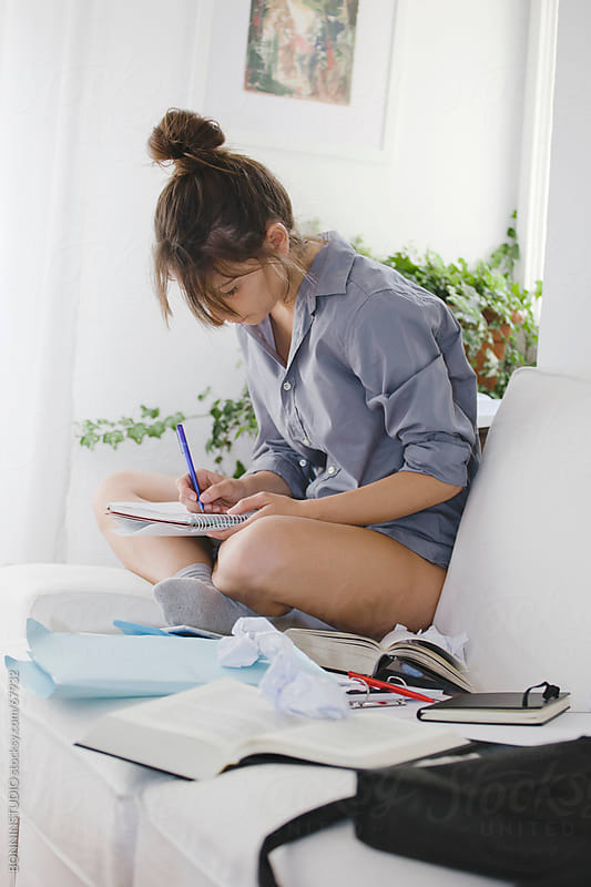Relaxing woman sitting on couch while studying for exam at home .  She is writing. by BONNINSTUDIO for Stocksy United