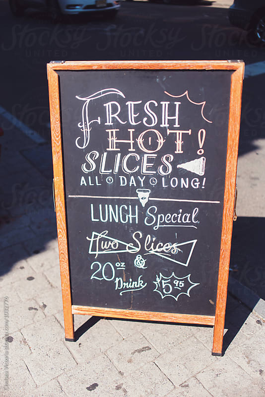A sign outside of a shop for pizza by Chelsea Victoria for Stocksy United