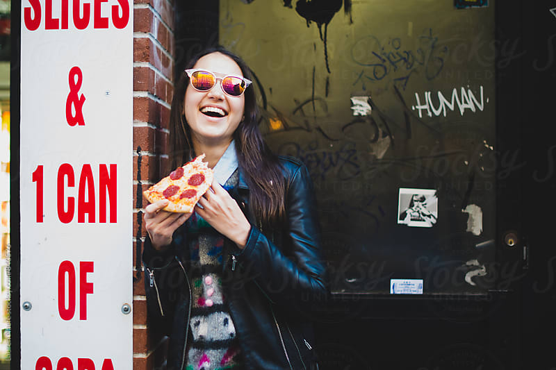 Young woman eating pizza by Lauren Naefe for Stocksy United