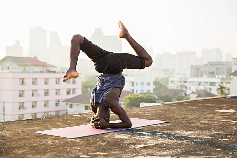 Man doing a yoga practice headstand on a city building rooftop  by Jovo Jovanovic for Stocksy United