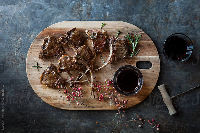 Pan seared lamb cutlets  on wooden platter by Nadine Greeff for Stocksy United