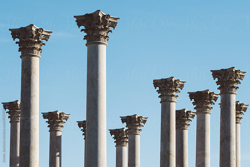 A grouping of corinthian columns against a clear blue sky. by James Jackson for Stocksy United