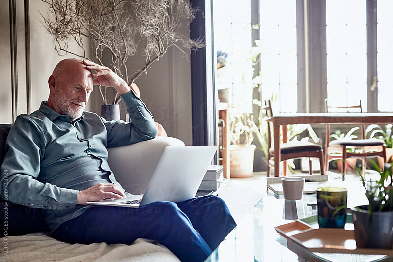 Senior Man Using Laptop At Home by ALTO IMAGES for Stocksy United