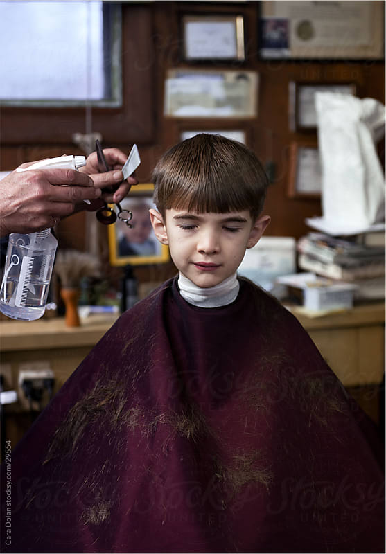 Boy sits quietly in barber's chair as he gets his hair cut by Cara Dolan for Stocksy United