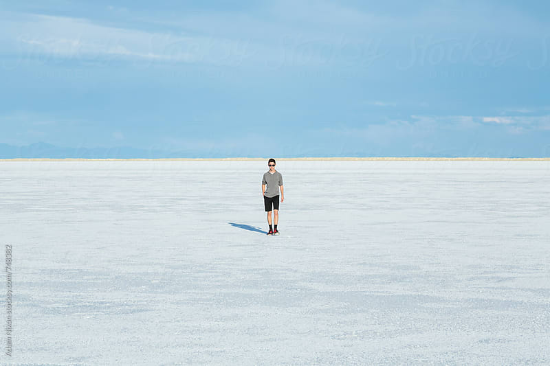 Teenage boy walking on the vast salt flats of Utah by Adam Nixon for Stocksy United
