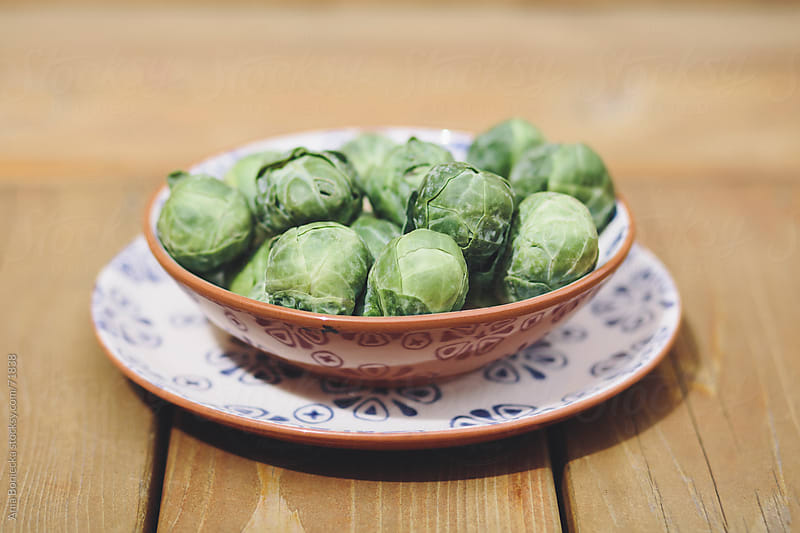 Brussels sprouts in a bowl outside by Ania Boniecka for Stocksy United