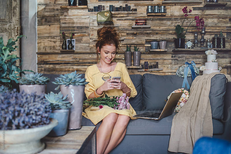 Florist Using a Mobile Phone in a Flower Shop by Lumina for Stocksy United
