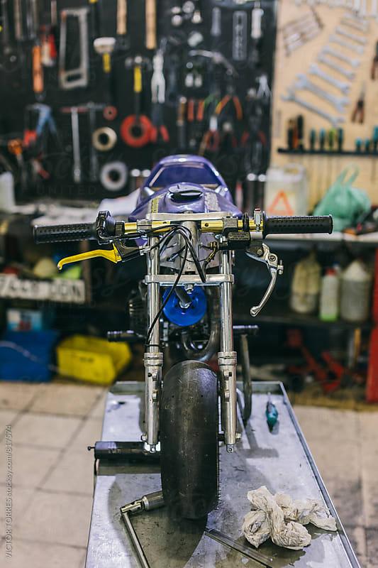 Mini Bike in the Repair Workshop by VICTOR TORRES for Stocksy United
