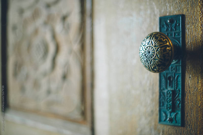 Old Metal Doorknob on a Carved Wood Door by Briana Morrison for Stocksy United